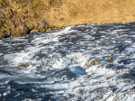 Streaming river at top of Skogafoss waterfall with snow and ice in winter season in Iceland