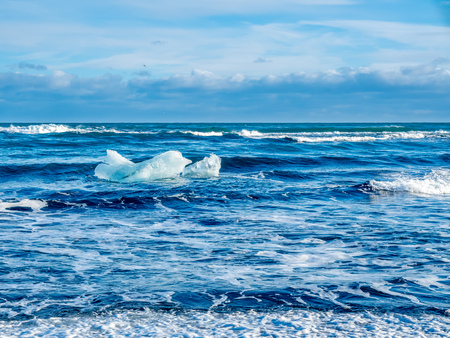 Large ice pieces with ocean wave in winter season at black sand diamond beach in Iceland Stock Photo