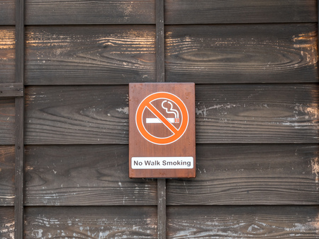 Non-smoking sign on wooden wall for background