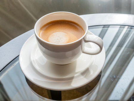 Cup of coffee on round glass table with natural window light in hotel room with cityscape view behind transparent curtain