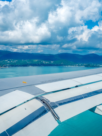 Island, sea, beach and cloudy blue sky view from aircraft window with its right wing