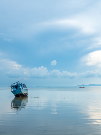Fisherman boat aground over shallow sea water in evening under cloudy blue sky at island in Thailand Stock Photo