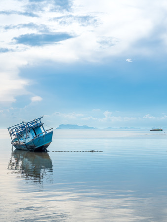 Fisherman boat aground over shallow sea water in evening under cloudy blue sky at island in Thailand Editorial