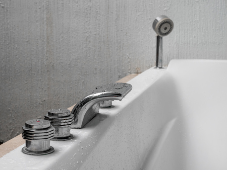 Cold and hot taps regulates in whirlpool bathtub with shower in white ceramic tub