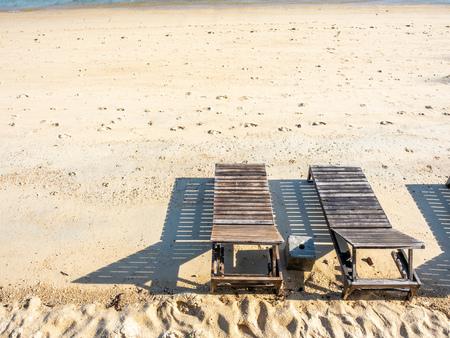 Wooden benches on white sand beach in summer season, Samui island, Thailand