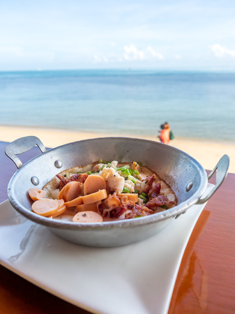 Fried egg with sausage, ham and bacon on private pan with seascape view in summer season at Samui island, Thailand Archivio Fotografico