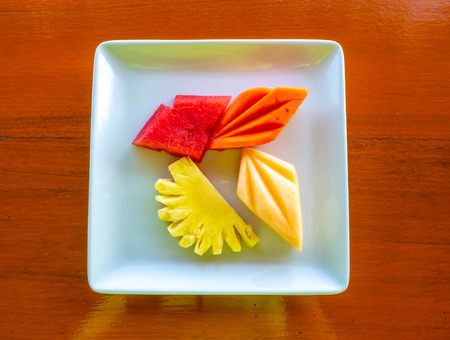 Four kinds of topical fruit, watermelon, melon, papaya and pineapple on white dish 스톡 콘텐츠