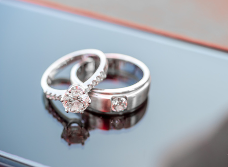 Twee diamanten trouwringen reflecteren op glas