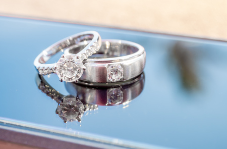 Two diamond wedding rings reflect on glass