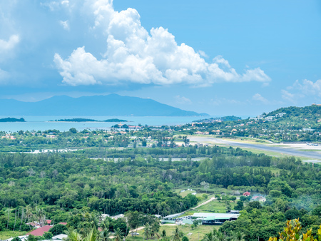 Viewpoint to runway at Samui airport with cityscape view of Samui island, Suratthani, Thailand, in summer season, under cloudy blue sky