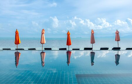 Umbrellas reflect with pool water with seascape view under cloudy blue sky in summer season at Samui island, Thailand Banco de Imagens