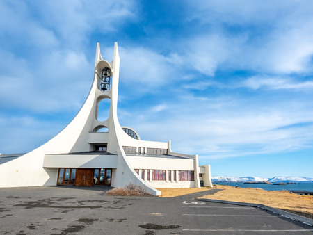 Stykkisholmur church on hill at center of town under cloudy blue sky, Iceland