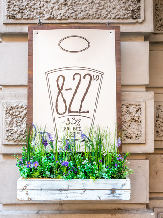 Discount price sign with opening hour at front of shop in Russia with flowers pot below Stockfoto