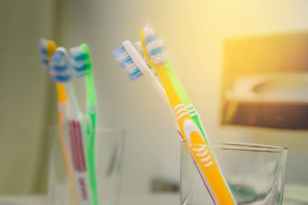 Set of brushes for teeth, teethbrushes for all family image in bathroom, in a glass cup. Multicolour dental hygiene daily protection toothbrush teeth care medicine modern. Background copy paste .