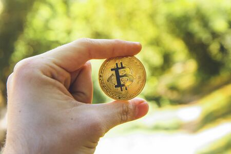 Hand holding a golden bitcoin , blurred background of wood ,forest , park.  concept of modern exchange value, new electronic money virtual pay , future concept. Used for investing in stocks and market