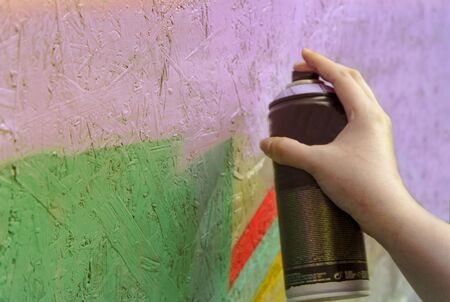 Graffiti artist painting with aerosol spray on the wall, wooden wall rustic Stock fotó