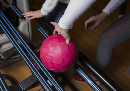 Close-up on teen children hand holding bowling ball against bowling alley - Image. Cheerful Kids are  ready to play - Image.  The bowling alley return machine system concept copy space design