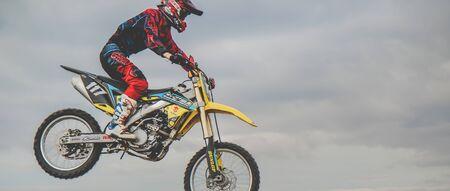 MX moto cross racing - Bike Rider riding on dirt track - extreme jump. Extreme Motocross.v Stockfoto