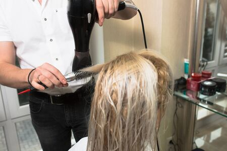 Young blonde attractive woman at hairdresser. Health And Beauty. Close-up of wet gray silver hair dryer, concept cut salon, female stylist. Comb Master prepares the client to restore the procedures