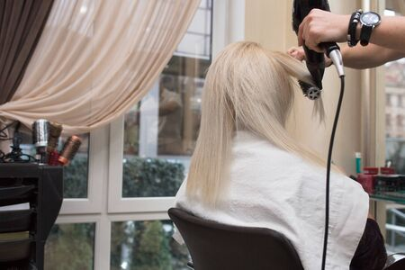 Young Beauty blonde attractive woman at hairdresser. Close-up of gray silver platinum comb hair dryer, concept cut salon, female stylist. Master prepares the teen client to restore the procedures