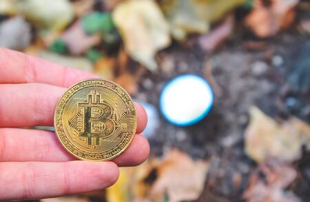 Hand holding Golden and silver bitcoin in autumn in forest , park .Modern exchange value, electronic money virtual pay , Used for investing in stocks and market in autumn , brown leaves