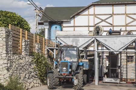 Modern agro-industry of  granulating and producti winery , wine making . Blue tractor loaded with grapes, grind squeeze fermentation  compressing granulation technology for granary , fabric .
