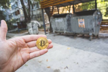 Hand holding a golden bitcoin , blurred background of trash , recycling cans, Concept of failing low modern exchange value, money virtual pay , future concept. Used for investing in low bad  stocks .