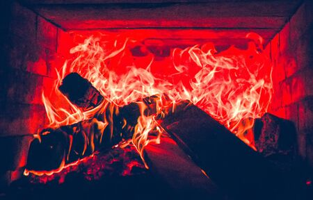 A fire burns into fireplace in red yellow big flames.
