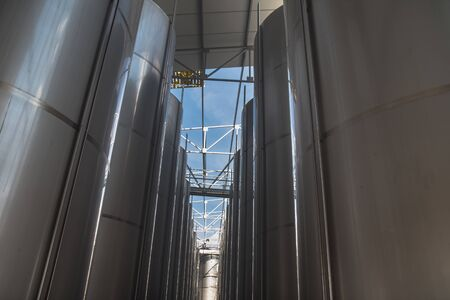 Modern  storage technology agro-industry, metal containers for grain business  granary trail perspective . Grain-drying Complex, Commercial  Seed Silos in Summer , sunny day, blue sky, white clouds