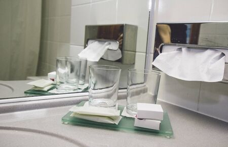 Water tap bath in modern hotel luxury leisure service. Hotel room service dental wash glass and soap hygienic person cleaning washing. Paper towels sheet towels refreshing napkins.