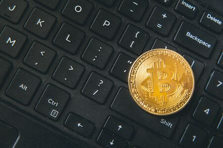 Bitcoin coin placed on modern black notebook keyboard. Close-Up photo Bitcoin , exchange virtual value, crypto digital money.Stock trading through internet.Selling big amounts, real estate. 版權商用圖片