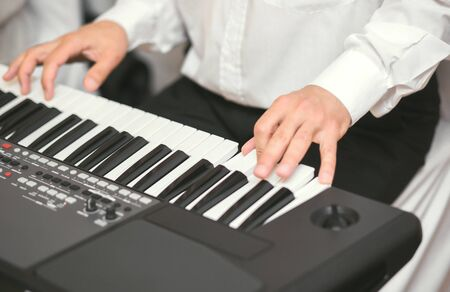 Hands of male musician playing at synthesizer. Mens arms plays solo of music or new melody. Close up fingers of pianist at the piano keys. Slow motion Top view.