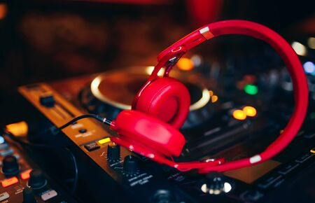 Closeup pair of Cheer red headphones for DJ.cd mp4 music deejay mixing desk music party in nightclub. Club console for experiments with music.