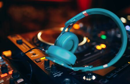 Closeup pair of aqua blue emerald green headphones for DJ.cd mp4 music deejay mixing desk music party in nightclub. Club console for experiments with music.