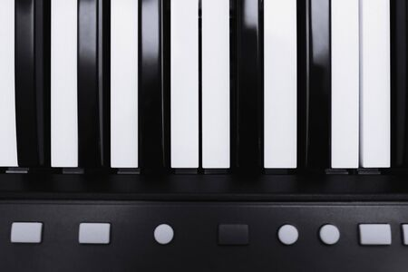 piano or electronic synthesizer (piano keyboard) background Midi keyboard and controller with faders and buttons. Concept of close texture pattern music design banner