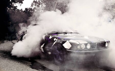 Moldova 25.09.2019. Sport modern Stance Car racing car drifting with smoke drift burnout, big colourful green blue clouds with clean wheels and burning tires . Extreme street stunts.   Stockfoto