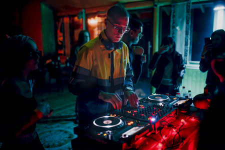 Chisinau, Moldova 11.10.2019. Rave techno DJ plays concert set with CD player turn table & Pioneer sound mixer surrounded by dancing people crowd minimal tracks party mix Redactioneel