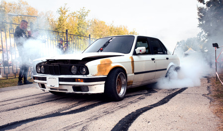 Moldova 25.09.2019. Sport modern Stance Car racing car drifting with smoke drift burnout, big colourful green blue clouds with clean wheels and burning tires . Extreme street stunts.