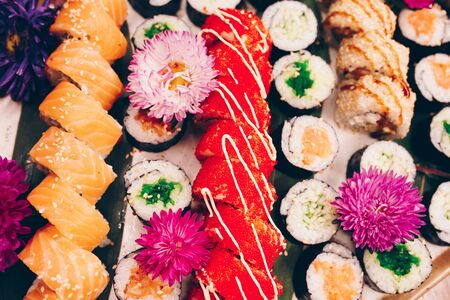 A large set of Delicious sushi rolls view from above Flat Lay . A lot assortment Philadelphia roll Dishes from Japanese raw fish  in one plate in traditional restaurant. Copy Space Japan menu service