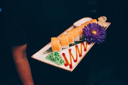 Close-up Hand Waiter holding Set Delicious fresh Sushi slate plate, Japanese raw fish   in traditional restaurant. Philadelphia flesh Rolls served on plate in sushi bar. Copy Space Japan menu service