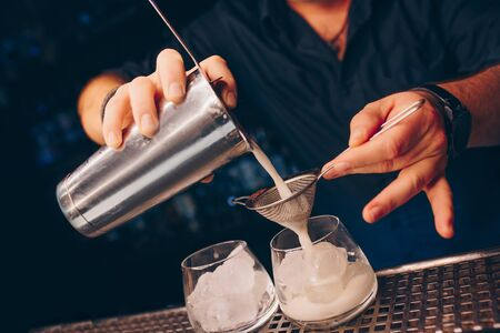 Bartender pouring using strainer White healthy Cocktail drink on a bar counter . Professional view . Trendy stylish alcoholic drink . Design people and luxury concept service barman in nightclub