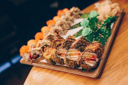 Large set of Sushi Rolls Warm Ebi Sake Unagi Spring. A lot assortment Philadelphia roll Dishes from Japanese raw fish in one plate in traditional restaurant. Japan food menu service Stock Photo