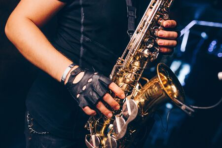 Boys Band saxophone section at event , jazz player male playing on Saxophone, music instrument played by man saxophonist  musician at  folk classical . Alto sax hands Closeup banner