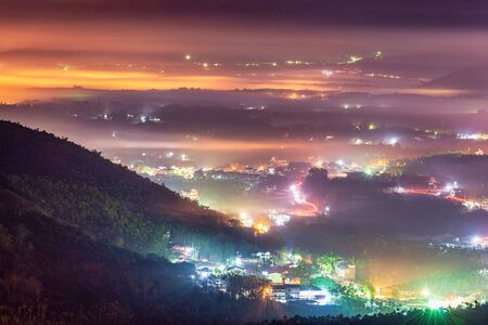 Night scenery from a viewpoint in Jinlongshan with lights from houses on hilltops, fog settled over the valleys and mountain silhouettes in a mystical atmosphere, in Nantou, Taiwan Zdjęcie Seryjne