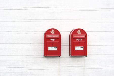 2 red post boxes and  and white wall in denmark photo