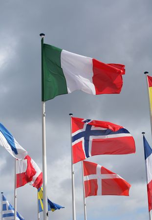 symbolization: european flags in the wind and sun with gray sky