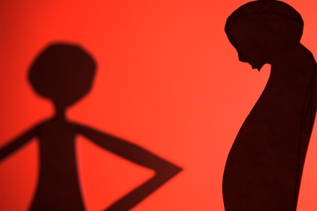 embarassed: man and woman silhouette cut in small rudimentary figures  in paper , shot with colorfull background Stock Photo