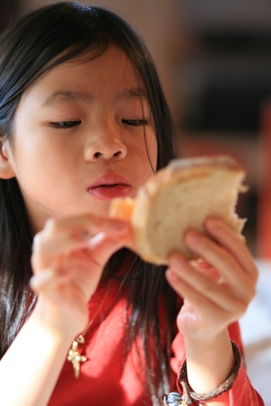 close up of hungry child eating bread photo