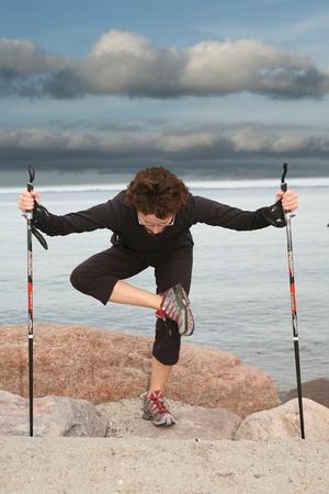 女性のデンマークのビーチでノルディックウォー キングをトレーニング