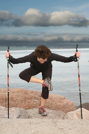 woman training nordic walking on a beach in denmark